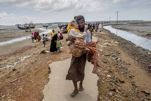 "A Rohingya Muslim man Abdul Kareem walks towards a refugee camp carrying his mother Alima Khatoon after crossing over from Myanmar into Bangladesh, at Teknaf, Bangladesh, Saturday, Sept. 16, 2017. United Nations agencies say an estimated 409,000 Rohingya Muslims have fled to Bangladesh since Aug. 25, when deadly attacks by a Rohingya insurgent group on police posts prompted Myanmar's military to launch ""clearance operations"" in Rakhine state. Those fleeing have described indiscriminate attacks by security forces and Buddhist mobs. (AP Photo/Dar Yasin)"