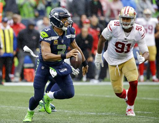 Seattle Seahawks quarterback Russell Wilson, left, scrambles away from San Francisco 49ers' Arik Armstead late in the second half of an NFL football game, Sunday, Sept. 17, 2017, in Seattle. (AP Photo/Elaine Thompson)