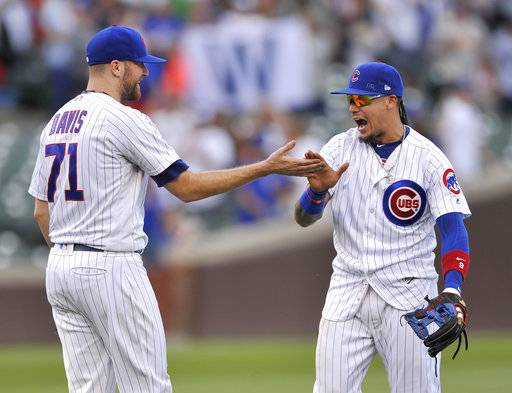 Chicago Cubs closing pitcher Wade Davis (71) celebrates with teammate Javier Baez right, after defeating the St. Louis Cardinals in a baseball game Sunday, Sept. 17, 2017, in Chicago. (AP Photo/Paul Beaty)