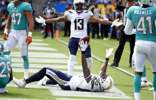 Los Angeles Chargers tight end Antonio Gates, bottom, celebrates his touchdown catch with wide receiver Keenan Allen (13) during the second half of an NFL football game against the Miami Dolphins Sunday, Sept. 17, 2017, in Carson, Calif. With the catch, Gates broke the record previously held by Tony Gonzalez (111) for most touchdown receptions by a tight end in NFL history. (AP Photo/Denis Poroy)