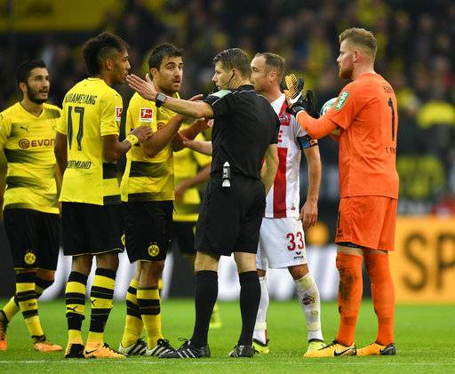 Referee Patrick Ittrich gives a goal by Dortmund's Sokratis, left, after a decision by the video referee during the German Bundesliga soccer match between Borussia Dortmund and 1.FC Cologne in Dortmund, Germany, Sunday, Sept. 17, 2017. (AP Photo/Martin Meissner)