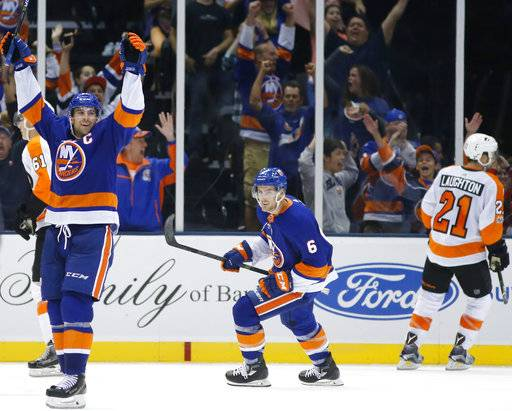 New York Islanders center and captain John Tavares, far left, celebrates after scoring a game-winning goal in overtime in a preseason NHL hockey game against the Philadelphia Flyers in Uniondale, N.Y., Sunday, Sept. 17, 2017. The Islanders defeated the Flyers 3-2 in the first overtime period. New York Islanders defenseman Ryan Pulock (6) watches as Philadelphia Flyers center Scott Laughton (21) skates away. (AP Photo/Kathy Willens)