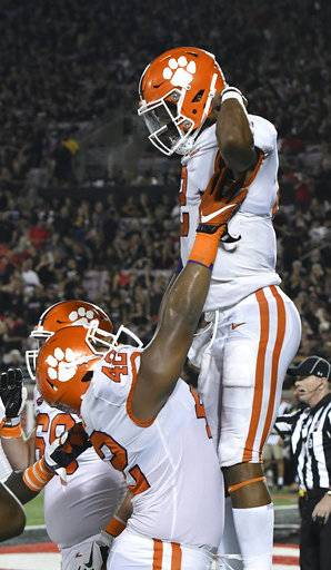 Clemson's linebacker Jarvis Magwood (46) holds up Kelly Bryant (2) following his touchdown during the second half of their NCAA college football game against Louisville, Saturday, Sept. 16, 2017, in Louisville, Ky. Clemson won 47-21. (AP Photo/Timothy D. Easley)