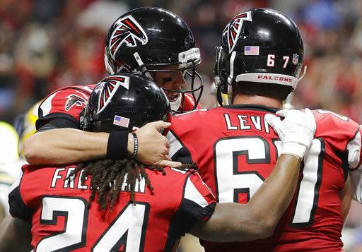 Atlanta Falcons running back Devonta Freeman (24) celebrates his touchdown run with Atlanta Falcons quarterback Matt Ryan and Atlanta Falcons offensive guard Andy Levitre (67) during the first of an NFL football game against the Green Bay Packers, Sunday, Sept. 17, 2017, in Atlanta. (AP Photo/David Goldman)