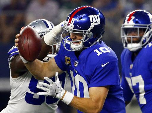 FILE - In this Sept. 10, 2017 file photo, Dallas Cowboys defensive end DeMarcus Lawrence (90) sacks New York Giants quarterback Eli Manning (10) in the first half of an NFL football game in Arlington, Texas. Manning felt the Cowboys' pass-rush wrath three times, but the issue for the Giants was that it's O-line was more of a 0-line, as in zero production.(AP Photo/Ron Jenkins)