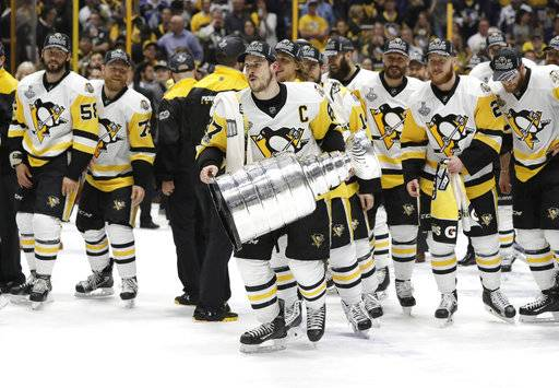 FILE - In this June 11, 2017, file photo, Pittsburgh Penguins' Sidney Crosby (87) celebrates with the Stanley Cup after defeating the Nashville Predators in Game 6 of the NHL hockey Stanley Cup Final, in Nashville, Tenn. Opportunistic, well-coached and talented, Pittsburgh has won eight consecutive playoff series to become the NHL's only back-to-back Stanley Cup champion of the salary-cap era and the first since the Detroit Red Wings in 1997 and 1998. Now everyone's trying to figure out how to stop the march of Sidney Crosby, Evgeni Malkin and the Penguins as they go for the three-peat. (AP Photo/Mark Humphrey, File)