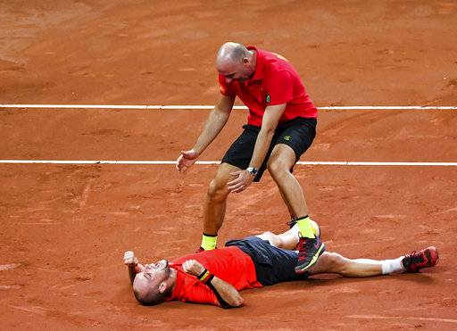 Belgium's Steve Darcis lays on the court celebrating with captain Johan Van Herck after winning against Australia's Jordan Thompson during a Davis Cup World Group semi-final tennis match in Brussels, Sunday, Sept. 17, 2017. (AP Photo/Geert Vanden Wijngaert)