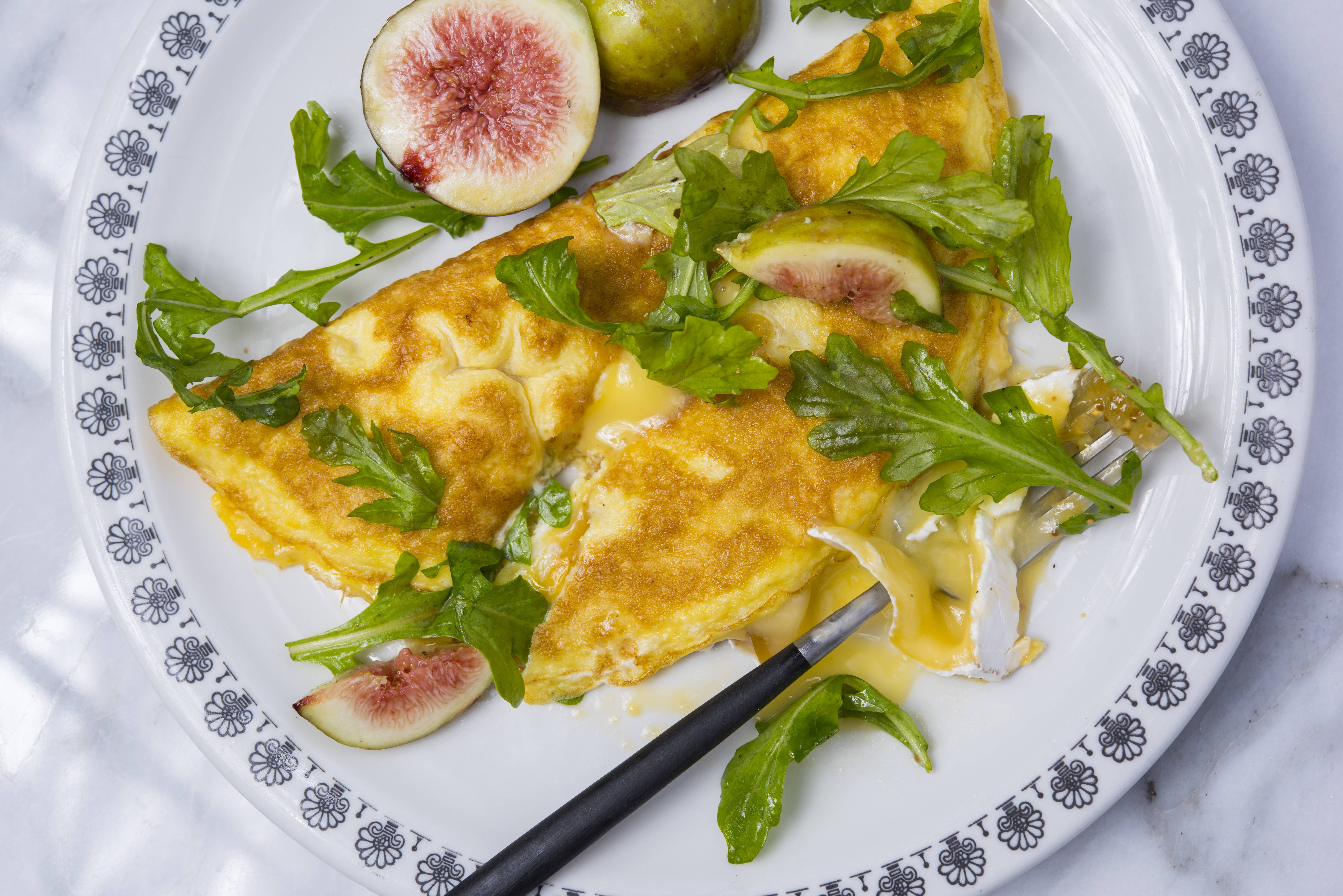 The combination of a not-too-sweet fruit, a pungent and melty cheese, soft egg with crisped edges and peppery greens makes these omelets a terrific option for brunch as well as dinner.