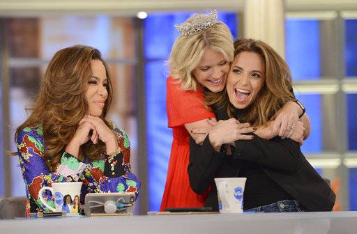 "Sara Haines, center, embraces Jedediah Bila, right, after Bila announces Monday, Sept. 18, will be her last day as co-host of ""The View."""