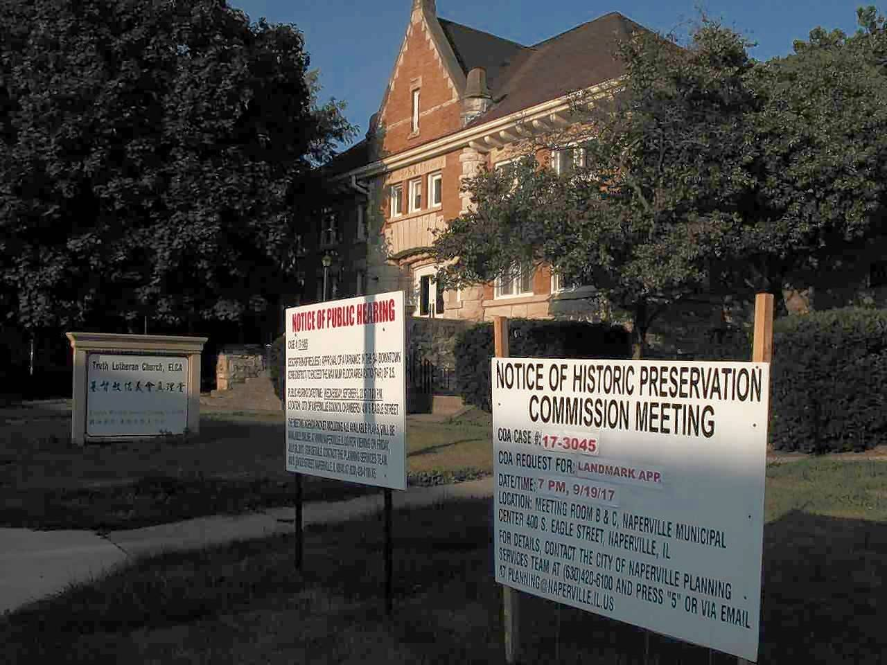 Signs in front of the old Nichols Library in Naperville inform passers-by of a development proposal, which since has been withdrawn, and an application for landmark status for the 119-year-old building. Landmark status was granted Tuesday night.