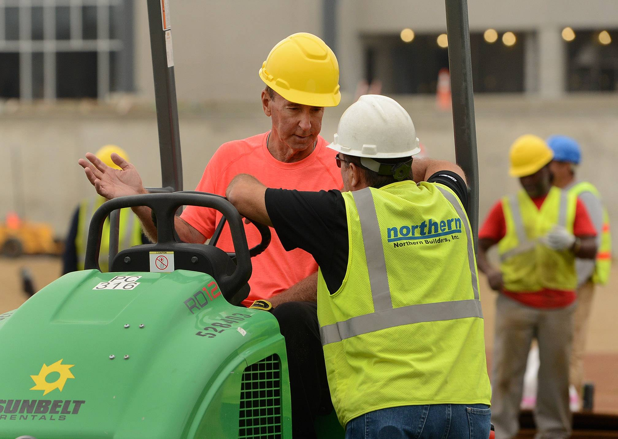 "Roger Bossard, also known as ""The Sodfather,"" used a machine roller to go back and forth over newly-placed pieces of infield sod at Impact Field in Rosemont. Here, he talks to a construction worker."
