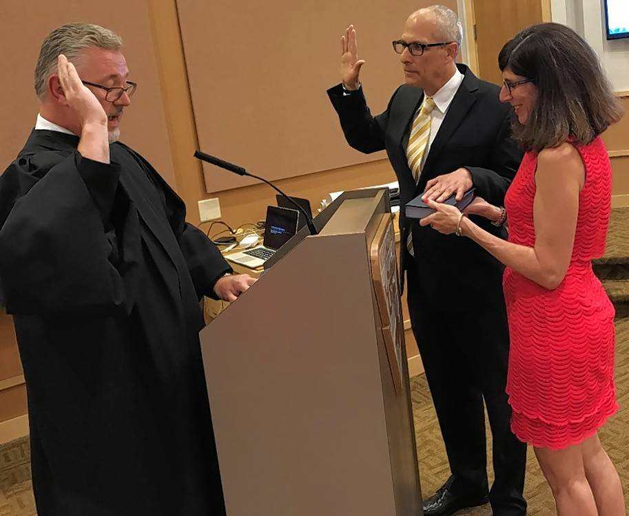 Judge and former Buffalo Grove Trustee Charles Johnson swears in new Trustee Eric Smith, who stands by his wife Judie.
