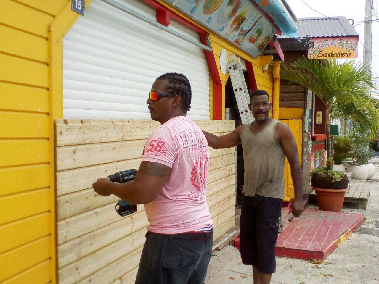 Men board up buildings Monday ahead of Hurricane Maria in Sainte-Anne on the French Caribbean island of Guadeloupe. Hurricane Maria grew into a Category 5 storm on Monday as it barreled toward a potentially devastating collision with islands in the eastern Caribbean.