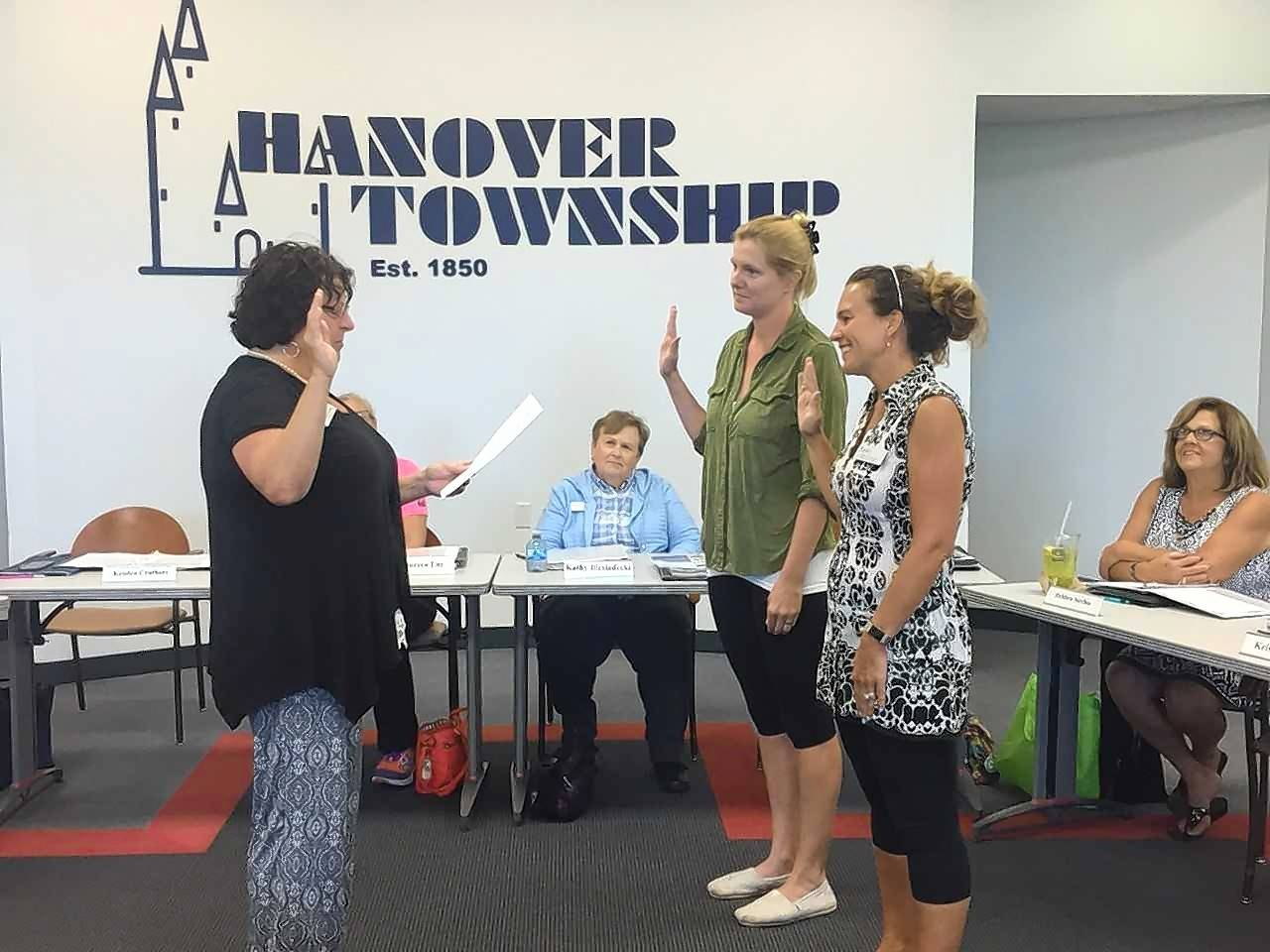 Hanover Township Clerk Katy Dolan Baumer swears in members Meghan Nelson and Kristen Cruthers.