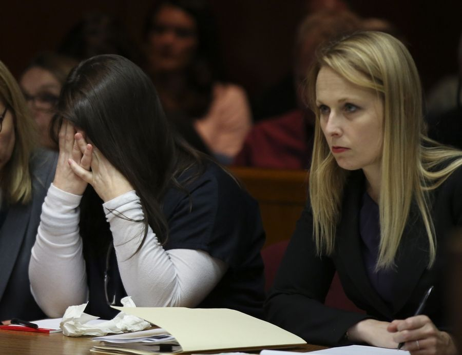 Elzbieta Plackowska hid her face on Sept. 12 as she listened to opening statements with Assistant Public Defender Kristen Nevdal, right, at the DuPage County courthouse in Wheaton. Plackowska is accused of murdering her son and a young girl she was baby sitting in October 2012.
