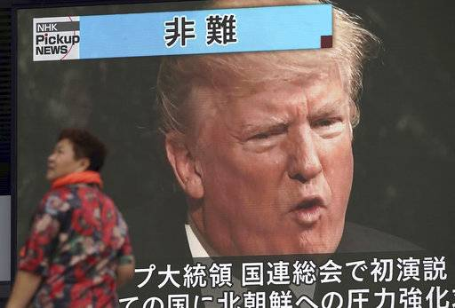 A woman walks past a TV screen showing U.S. President Donald Trump while reporting on his maiden address at the U.N. General Assembly, in Tokyo Wednesday, Sept. 20, 2017. Trump's threat before the world to obliterate North Korea left no doubt about his determination to stop the communist country's nuclear weapons buildup. (AP Photo/Eugene Hoshiko)