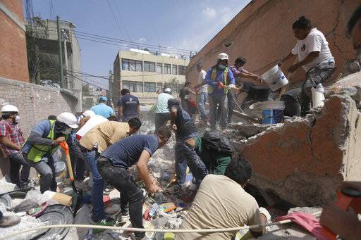 Rescue workers and volunteers search for survivors at the Ninos Heroes neighborhood in Mexico City, Tuesday Sept. 19, 2017. A magnitude 7.1 earthquake has stunned central Mexico, killing more than 100 people as buildings collapsed in plumes of dust. (AP Photo/Miguel Tovar)