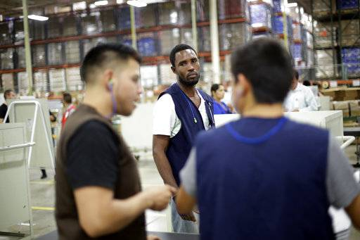 In this June 6, 2017 photo, Rodin St. Surin, of Haiti, looks on as coworkers talk on the floor of a factory in Tijuana, Mexico. St. Surin, 36, who left Brazil with hopes of joining a cousin in Miami, earns 1,500 pesos ($83) for a six-day week but has health coverage, paid vacation and a free shuttle to work. He sends his earnings to a caretaker for his three children in Haiti, who he hopes to bring to Tijuana. (AP Photo/Gregory Bull)