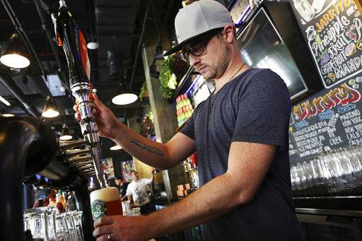 In this Sunday, Sept. 10, 2017 photo, Eric Ballard of Granby, Colorado, the group beverage manager for Sunset Hospitality, pours a beer at the Black Tap restaurant in Dubai, United Arab Emirates. Dubai long has been known for its clubbing scene and cocktail bars, but there's a new thirst for craft beer. New businesses are springing up and exotic brews are replacing the country's standard lagers.