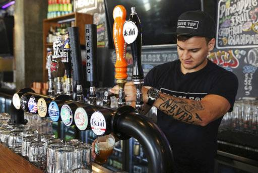 In this Sunday, Sept. 10, 2017 photograph, bartender Michael Zakharchenko, originally from Ukraine, pours a beer at the Black Tap restaurant in Dubai, United Arab Emirates. Dubai long has been known for its clubbing scene and cocktail bars, but there's a new thirst for craft beer. New businesses are springing up and exotic brews are replacing the country's standard lagers.