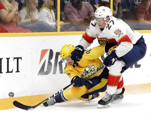 Florida Panthers center Nick Bjugstad (27) checks Nashville Predators defenseman Alexandre Carrier (45) into the boards during the third period of the second game in an NHL hockey preseason doubleheader Tuesday, Sept. 19, 2017, in Nashville, Tenn. The Predators won 3-2 in overtime. (AP Photo/Mark Humphrey)