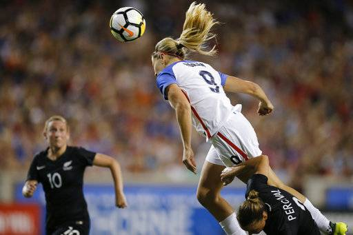 U.S. midfielder Lindsey Horan (9) heads in a goal over New Zealand defender Ria Percival (2) in the first half of an international friendly soccer match at Nippert Stadium in Cincinnati, on Tuesday, Sept. 19, 2017. (Sam Greene/The Cincinnati Enquirer via AP)