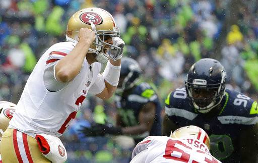 San Francisco 49ers quarterback Brian Hoyer, left, yells on the line of scrimmage in the second half of an NFL football game against the Seattle Seahawks, Sunday, Sept. 17, 2017, in Seattle. (AP Photo/Elaine Thompson)