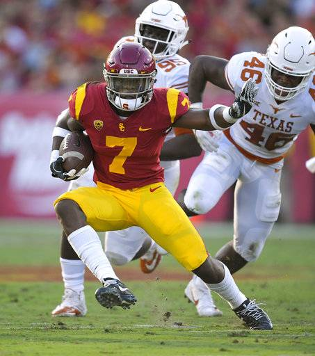 Southern California running back Stephen Carr, left, runs the ball as Texas defensive lineman Poona Ford, center, and linebacker Malik Jefferson defend during the first half of an NCAA college football game, Saturday, Sept. 16, 2017, in Los Angeles. (AP Photo/Mark J. Terrill)