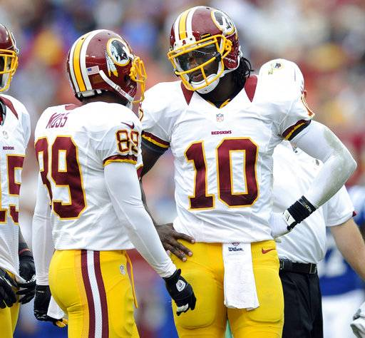 FILE - In this Aug. 25, 2012, file photo, Washington Redskins quarterback Robert Griffin III (10) talks with teammates Santana Moss (89)) during a preseason NFL football game against the Indianapolis Colts in Landover, Md. Moss, during his weekly radio appearance in Washington, says Griffin took credit for coach Mike Shanahan and offensive coordinator Kyle Shanahan being fired by the Washington Redskins in 2013. (AP Photo/Nick Wass, File)