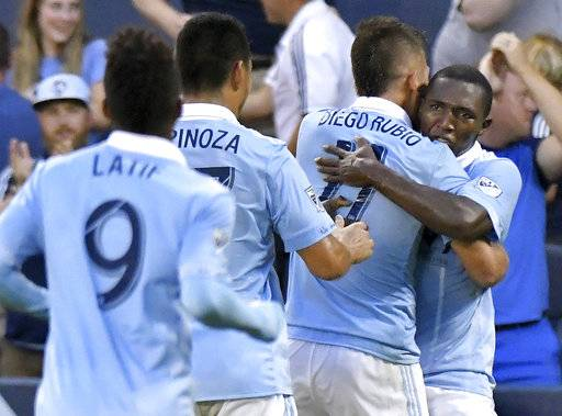 FILE - In this Aug. 9, 2017, file photo, Sporting Kansas City midfielder Jimmy Medranda, right, hugs midfielder Diego Rubio after Rubio scored against the San Jose Earthquakes during the first half of a U.S. Open Cup semifinal soccer game, in Kansas City, Kan. Sporting Kansas City host the New York Red Bulls in the U.S Open Cup final on Wednesday, Sept. 20, 2017. (John Sleezer/The Kansas City Star via AP, File)