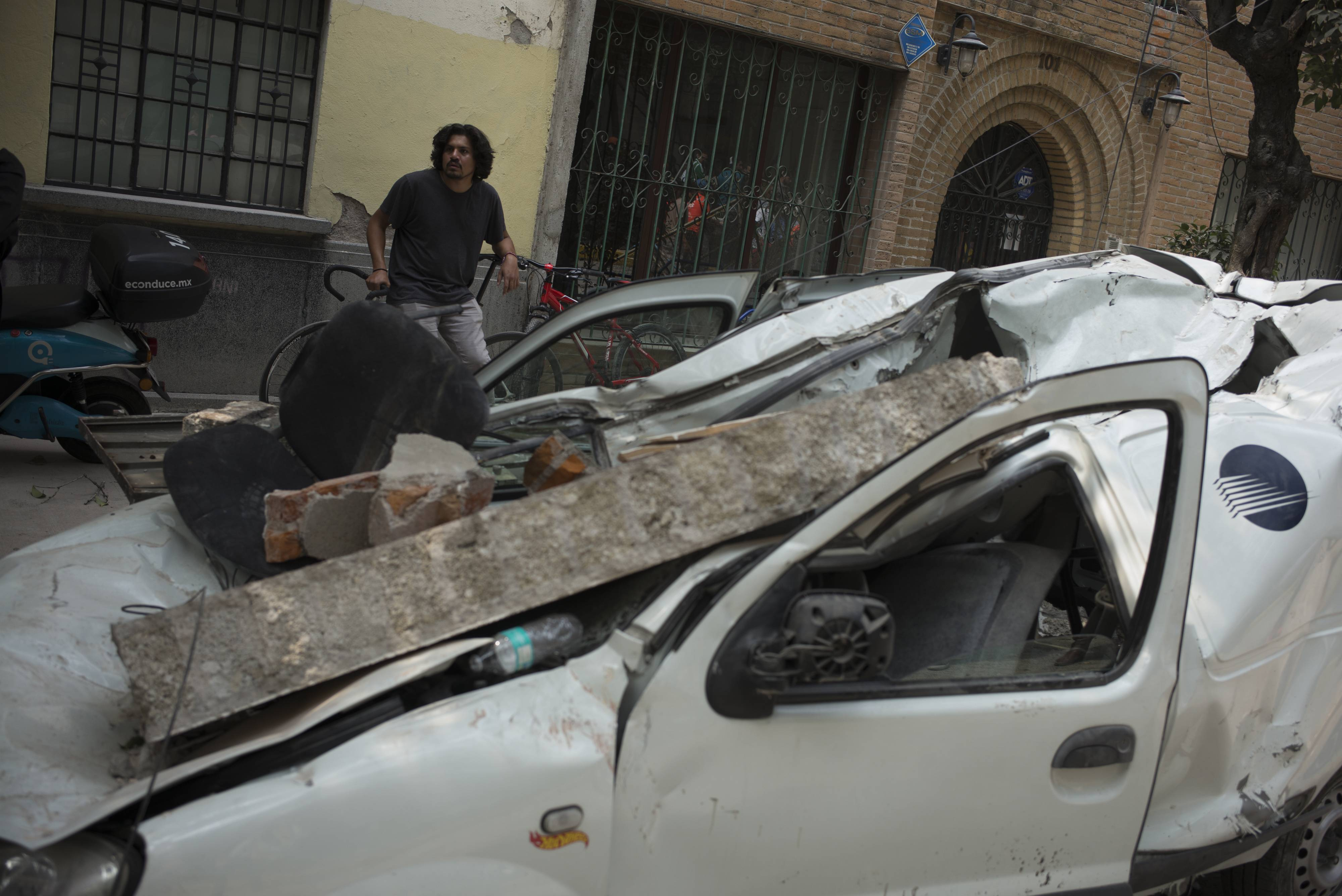 A vehicle is seen destroyed by debris Monday from a collapsed building following an earthquake in Mexico City.