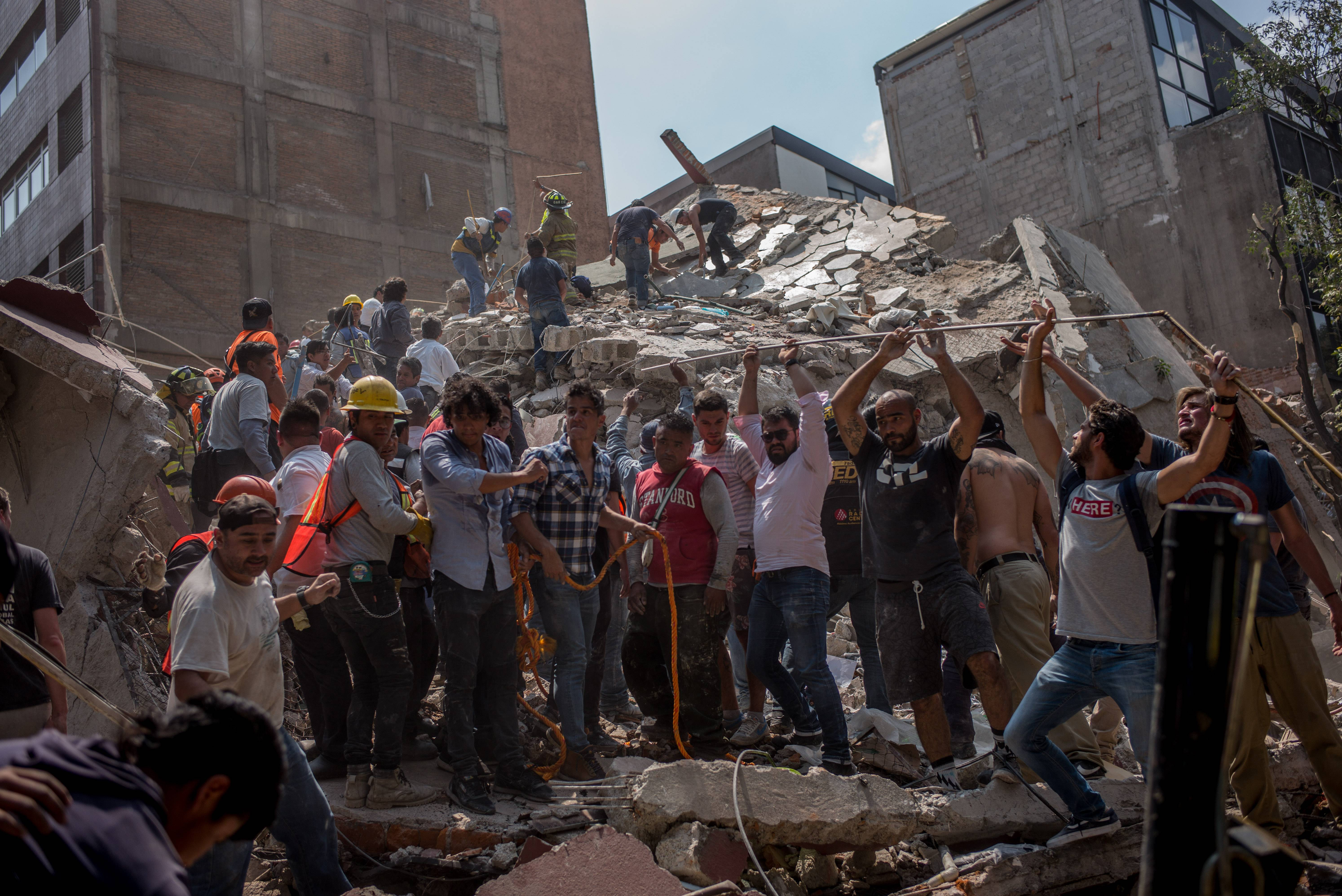 People remove debris from a collapsed building Monday following an earthquake in Mexico City.