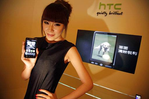 FILE - In this July 27, 2010, file photo, a Chinese model holds up a phone from Taiwan's HTC at a press conference in Beijing to introduce the brand into China's market. Google is biting off a big piece of device manufacturer HTC for $1.1 billion to expand its efforts to build phones, speakers and other gadgets equipped with its arsenal of digital services. The company is buying the HTC team that built the Pixel smartphone for Google in a cash deal, they said in a joint statement Thursday, Sept. 21, 2017. Google is also getting a non-exclusive license for Taiwan-based HTC's intellectual property to help support Pixel phones.