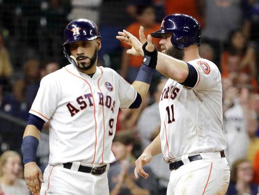 Houston Astros' Marwin Gonzalez (9) and Evan Gattis (11) celebrate after scoring on a double by Yuli Gurriel during the fourth inning of a baseball game against the Chicago White Sox Wednesday, Sept. 20, 2017, in Houston.
