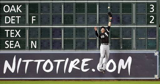Chicago White Sox left fielder Nicky Delmonico leaps to make the catch on a fly ball by Houston Astros' George Springer during the fifth inning of a baseball game Wednesday, Sept. 20, 2017, in Houston.