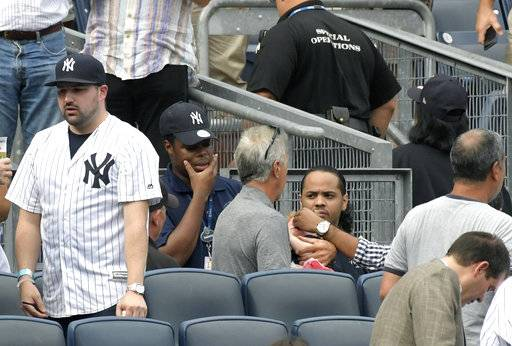 Baseball fans reacts as a young girl is tended to before she is carried out of the seating area after being hit by a line drive in the fifth inning of a baseball game between the New York Yankees and Minnesota Twins, Wednesday, Sept. 20, 2017, at Yankee Stadium in New York.