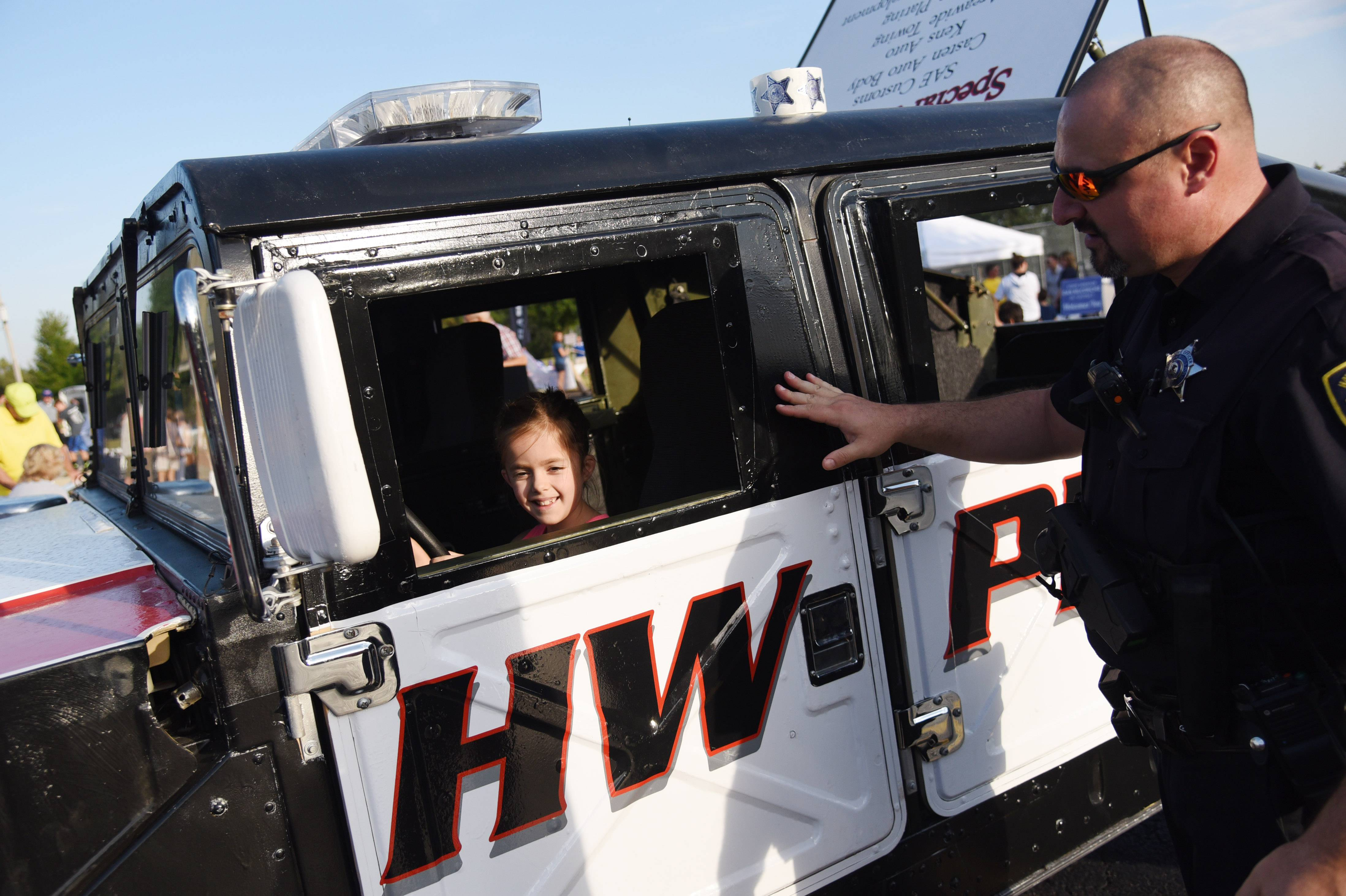 Seven-year-old Ellie Madsen, assisted by officer Mike Rossini, sits in a Hawthorn Woods police vehicle Thursday at Ela Township's second annual Township Day at Knox Park in Lake Zurich.