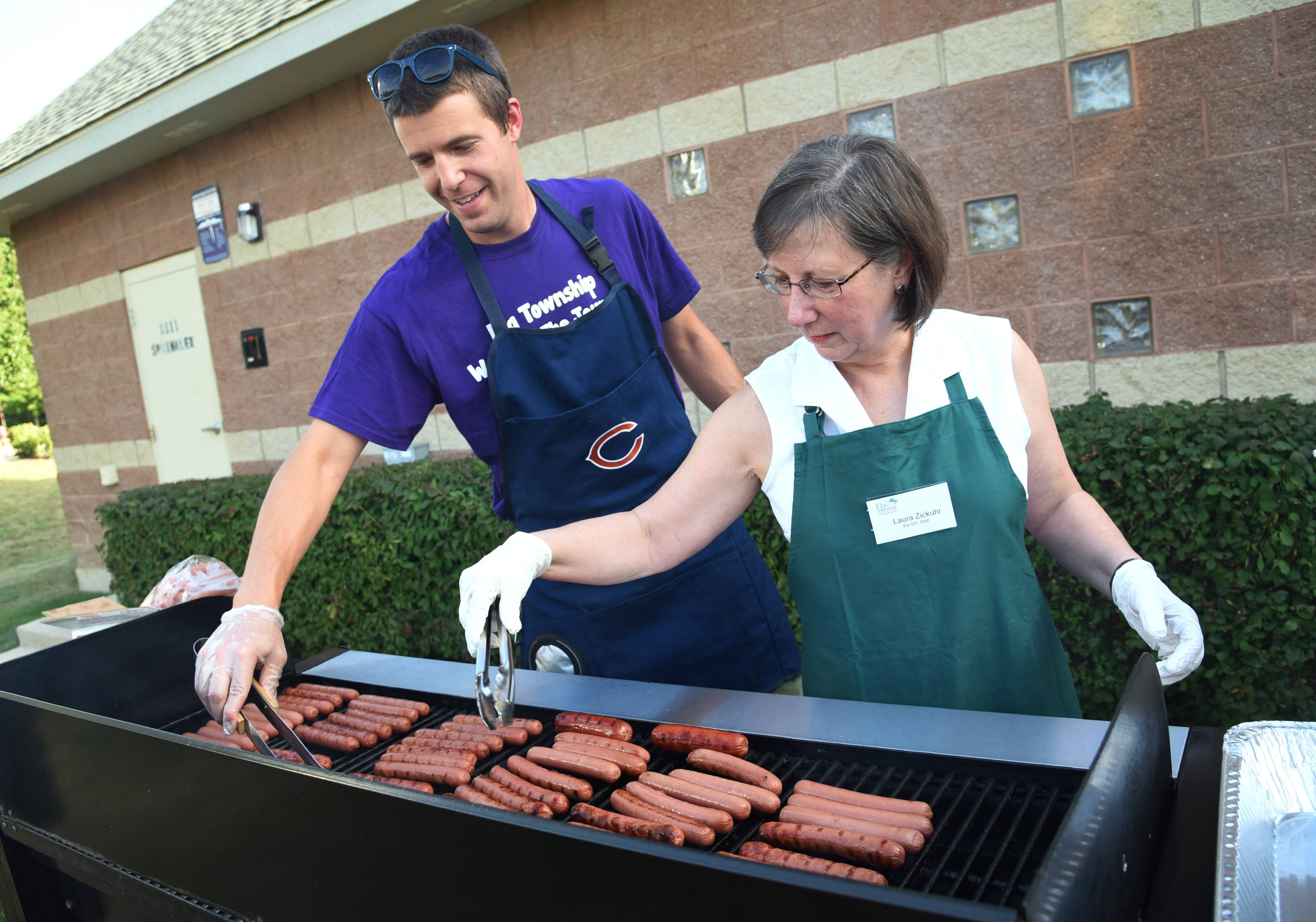 Ela 55+ staff members Jim Dalbec and Laura Zickuhr cook hot dogs Thursday for Ela Township's second annual Township Day.