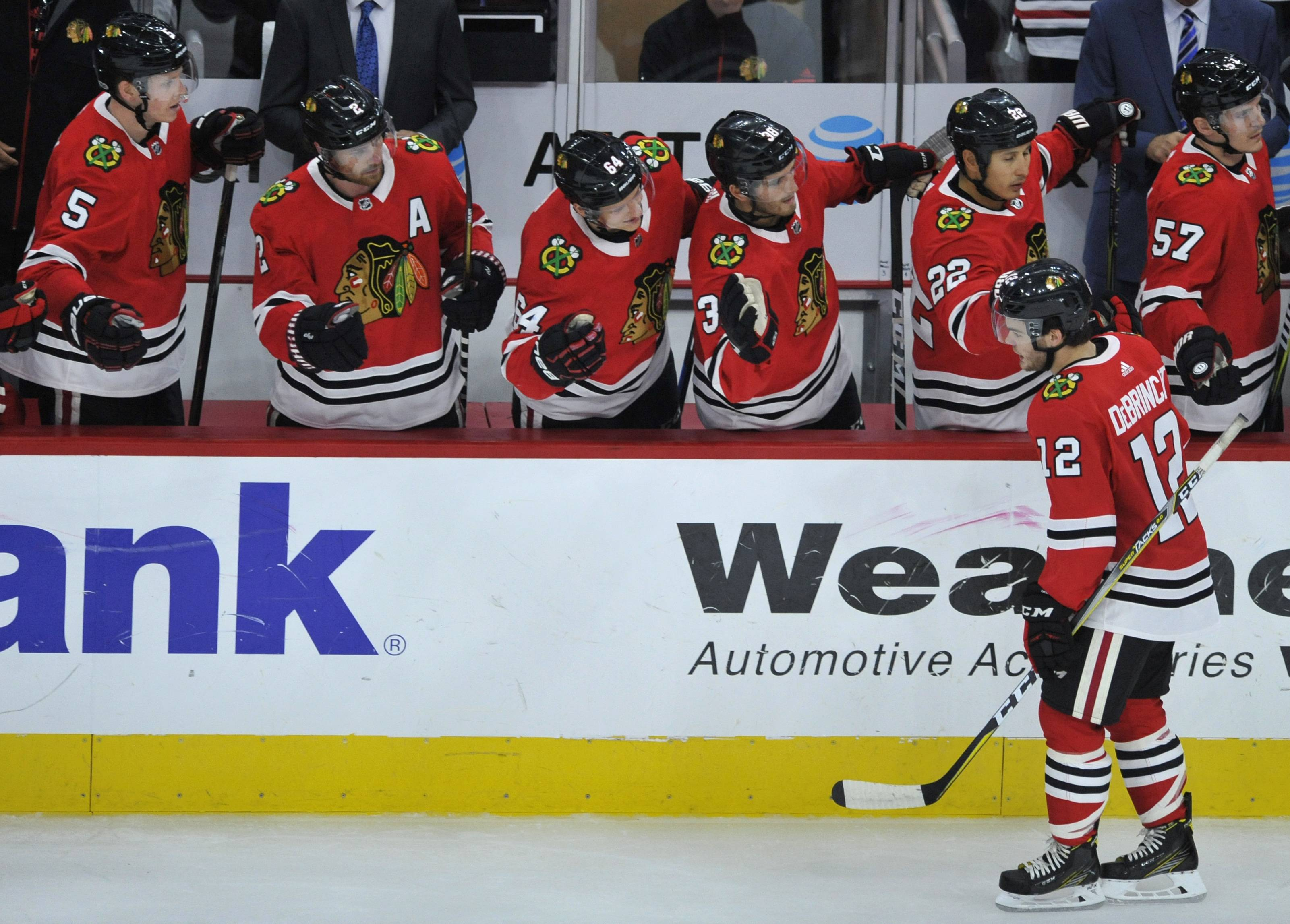 Chicago Blackhawks' Alex Debrincat (12) celebrates with teammates on the bench after scoring a goal during the second period of a preseason NHL hockey game against the Detroit Red Wings Thursday, Sept. 21, 2017, in Chicago. (AP Photo/Paul Beaty)