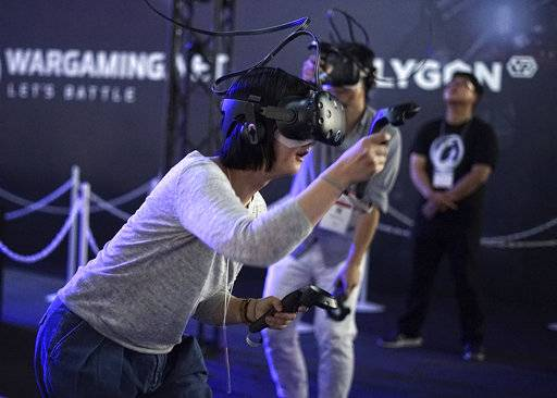 Visitors try out a game with a virtual reality headset device at the Tokyo Game Show in Chiba, near Tokyo, Thursday, Sept. 21, 2017. The Japanese video game industry is finding its way out of the doldrums, by adapting new technology for decades-old titles. And that energy was evident at the annual game show.