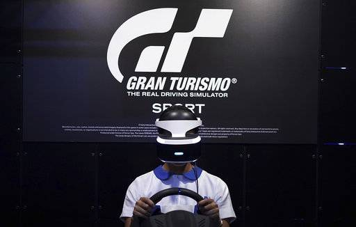 A woman tries out a PlayStation VR headgear device at the Tokyo Game Show in Chiba, near Tokyo, Thursday, Sept. 21, 2017. The Japanese video game industry is back, after suffering years of the doldrums, with decades-old titles being adapted for revamped technology. That energy was amply evident at the Tokyo Game Show, an annual event showcasing video games.