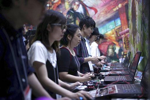Visitors try out games at the Tokyo Game Show in Chiba, near Tokyo, Thursday, Sept. 21, 2017. The Japanese video game industry is finding its way out of the doldrums, by adapting new technology for decades-old titles. And that energy was evident at the annual game show.