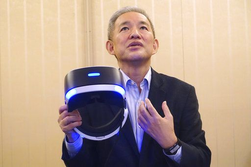 Atsuhi Morita, president of Sony Interactive Entertainment Japan, Sony's game division, holds a PlayStation VR headgear device as he answers a question during an interview at the Tokyo Game Show in Chiba, near Tokyo, Thursday, Sept. 21, 2017. Morita said Japanese culture is at the root of visual story-telling that began with manga comic books, went on to animation and films, and now allow for an interactive element in games.
