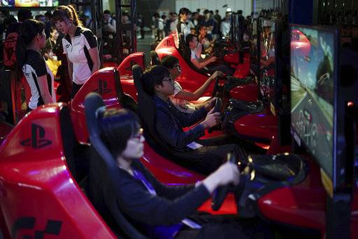 Visitors try out a car driving game at the Tokyo Game Show in Chiba, near Tokyo Thursday, Sept. 21, 2017. The Japanese video game industry is back, after suffering years of the doldrums, with decades-old titles being adapted for revamped technology. That energy was amply evident at the Tokyo Game Show, an annual event showcasing video games.