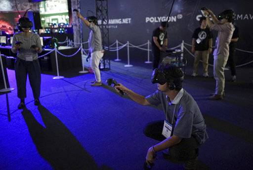 Visitors try out a game with a virtual reality headset device at the Tokyo Game Show in Chiba, near Tokyo, Thursday, Sept. 21, 2017. The Japanese video game industry is back, after suffering years of the doldrums, with decades-old titles being adapted for revamped technology. That energy was amply evident at the Tokyo Game Show, an annual event showcasing video games.