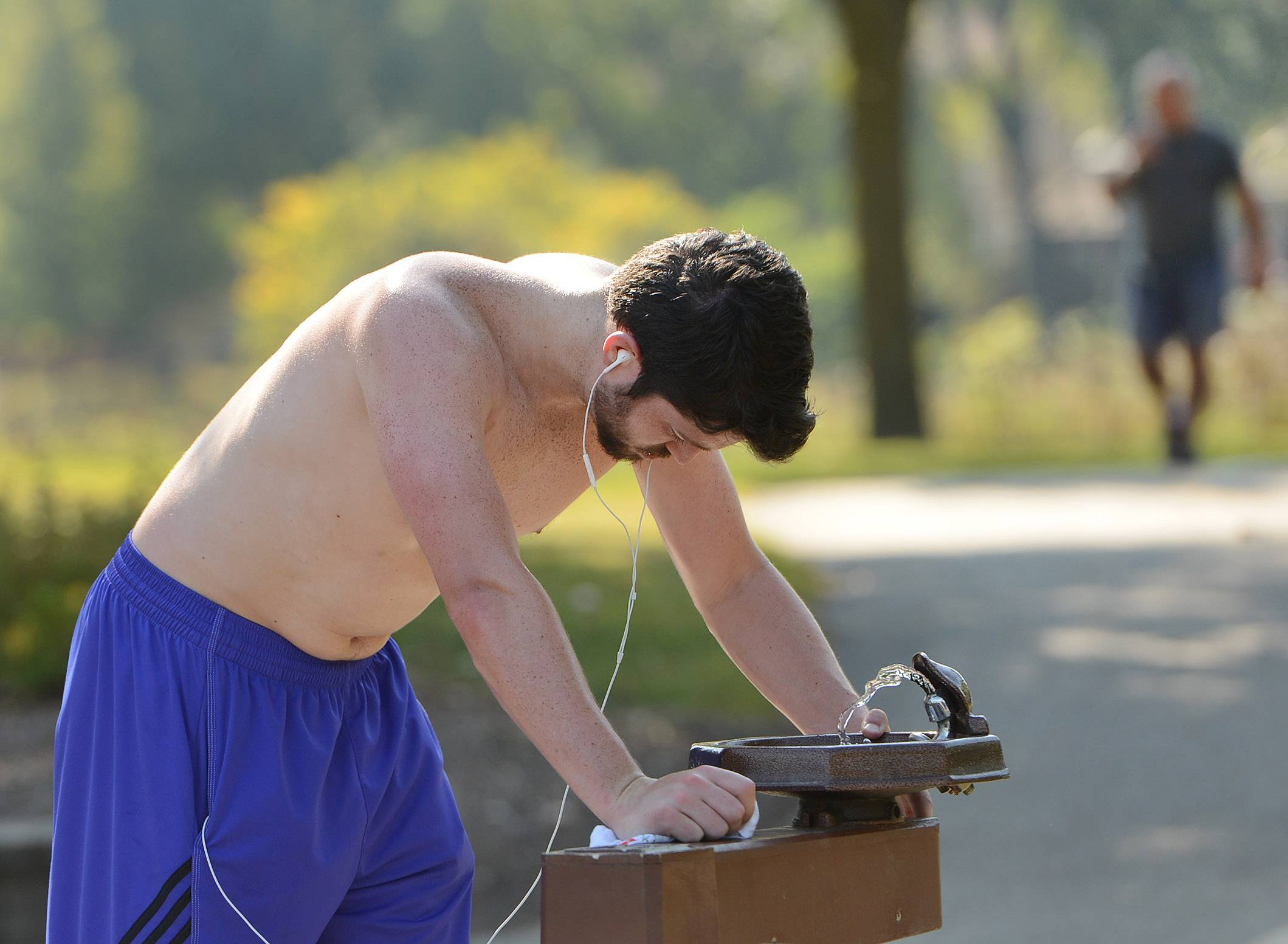 Chris McClellan of Buffalo Grove grabs some water from a fountain at Lake Arlington in Arlington Heights. McClellan says he likes to run on hot days to get a good sweat going. He runs three or four times a week.