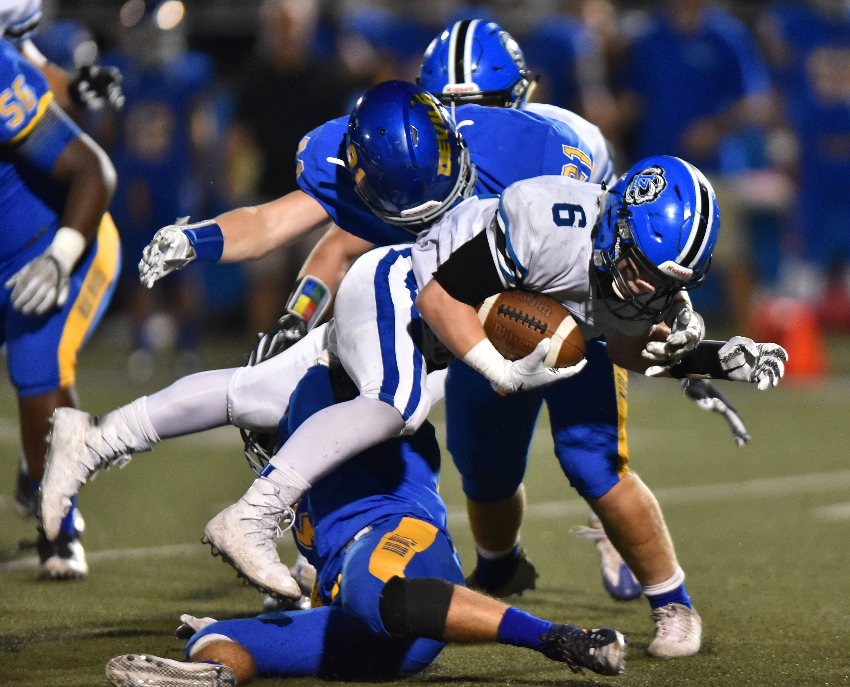 Lake Zurich's Joey Stutzman is tripped up by Warren's Caden Fox and Jared Keeter Friday in Gurnee.