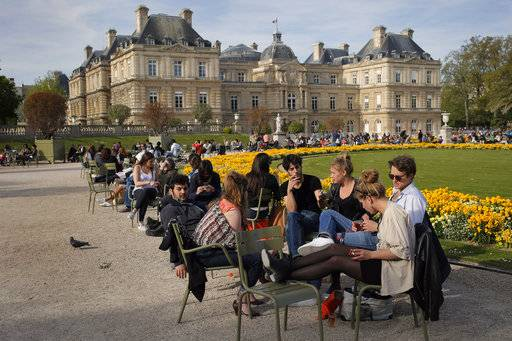 FILE - In this Thursday, May 5, 2016 file photo, Parisians take the sun in the Luxembourg Garden next the French Senate, seen in background, in Paris, France. On Sunday, France will elect nearly half its Senate, in a vote that is expected to illustrate the slide in President Emmanuel Macron's popularity since his election earlier this year.