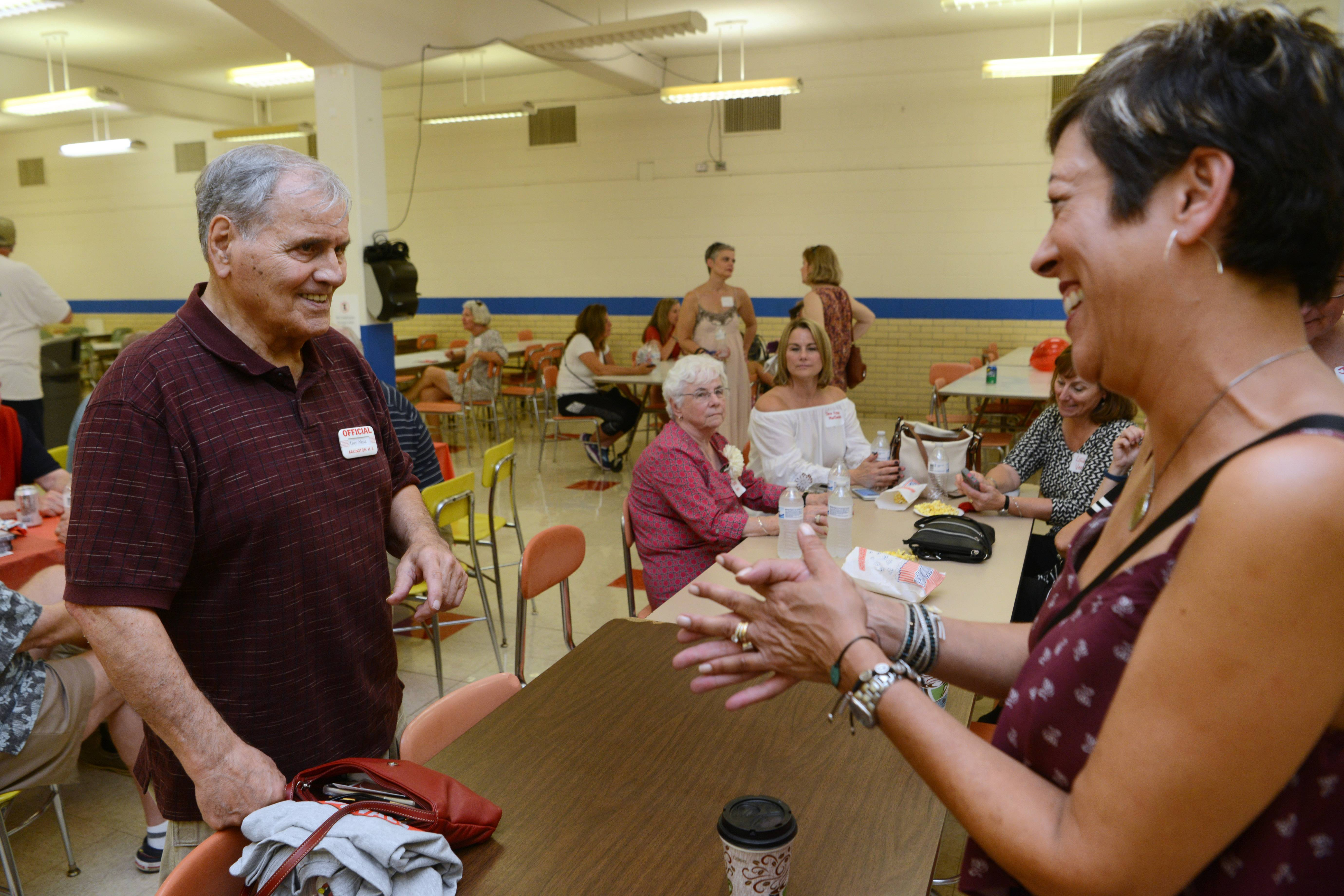 Former dean of students Guy Vena visits with Nancy Aiello Lynk of Arlington Heights, a member of the class of 1981, during the Arlington High School all-class homecoming, held Saturday at the former school building, which is now Christian Liberty Academy.
