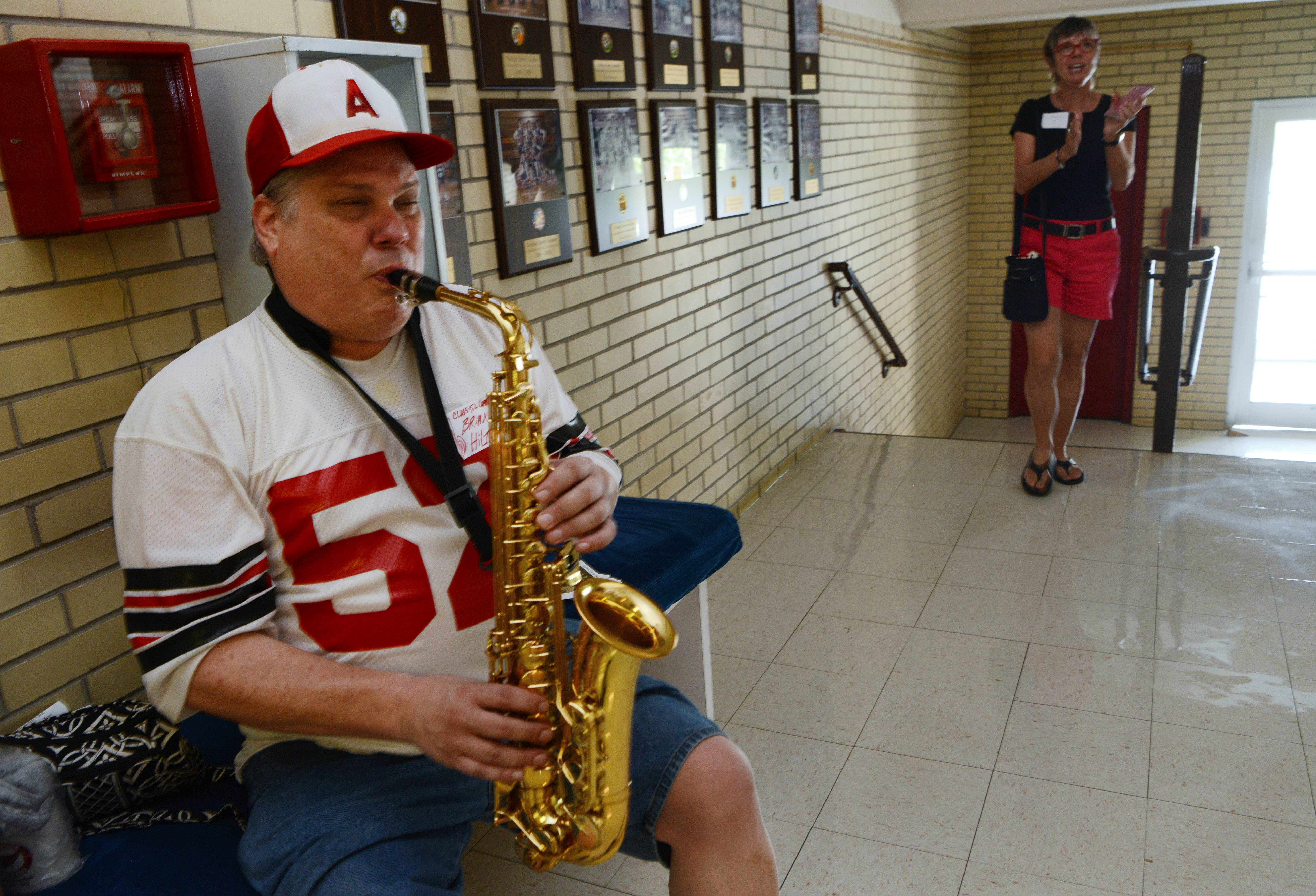 Brian Hilton, a member of the final graduating class of 1984, plays the school song on saxophone during the Arlington High School all-class homecoming, held at the former school building, which is now Christian Liberty Academy, in Arlington Heights Saturday.